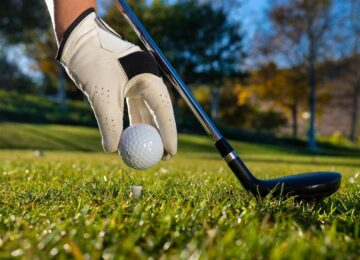 Gloved hand placing a golf ball on a tee next to a black golf club.
