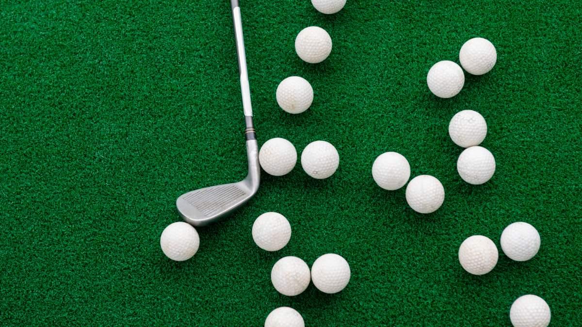 Golf club with golf balls lying on grass.