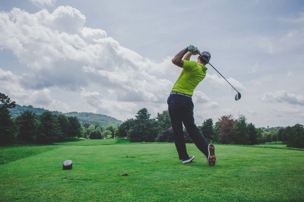 Man with his back to the camera in mid-swing on a golf course.