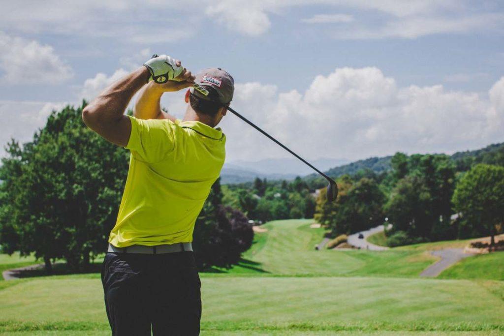 Man seen from behind swinging a golf club.