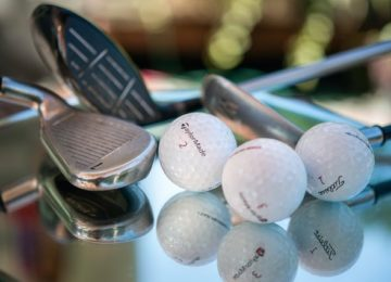 Golf balls and clubs on a glass surface.