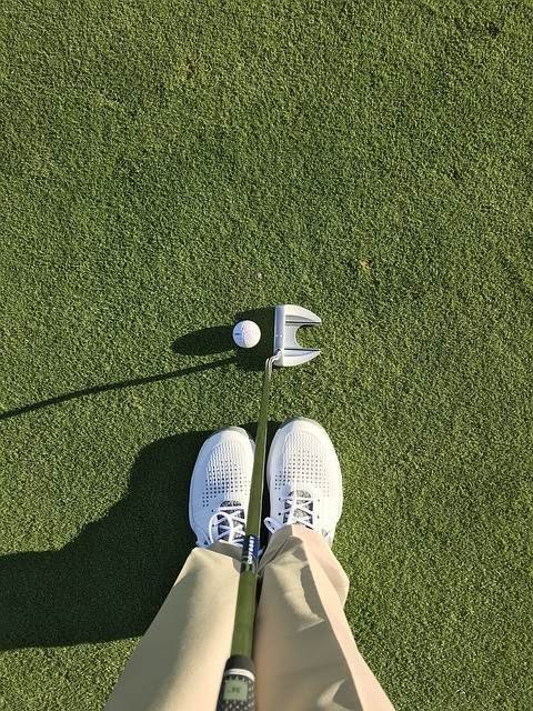 A person wearing khaki pants visible from the knee down standing beside a golf ball and holding a putter.
