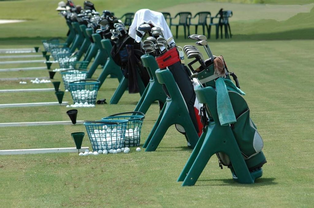 Golf bags and balls lined up at a driving range.