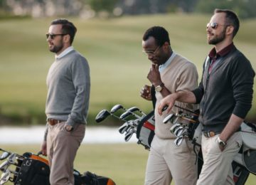 Three men on a golf course carrying golf bags