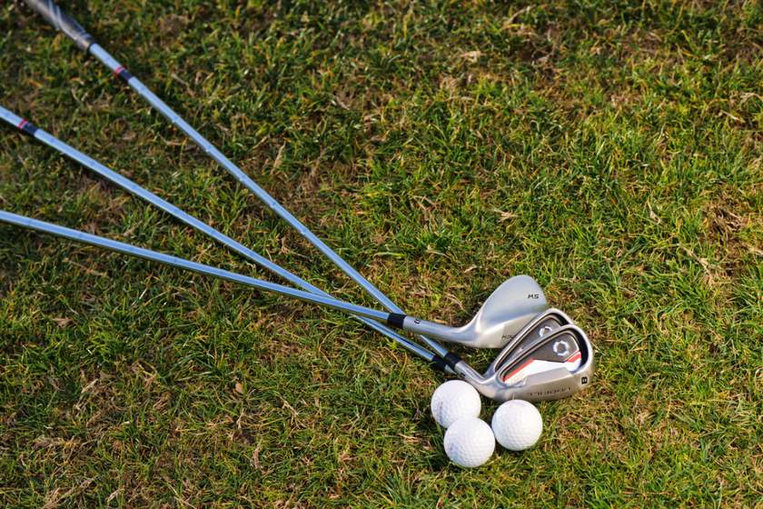 Three golf clubs and balls lying on grass.