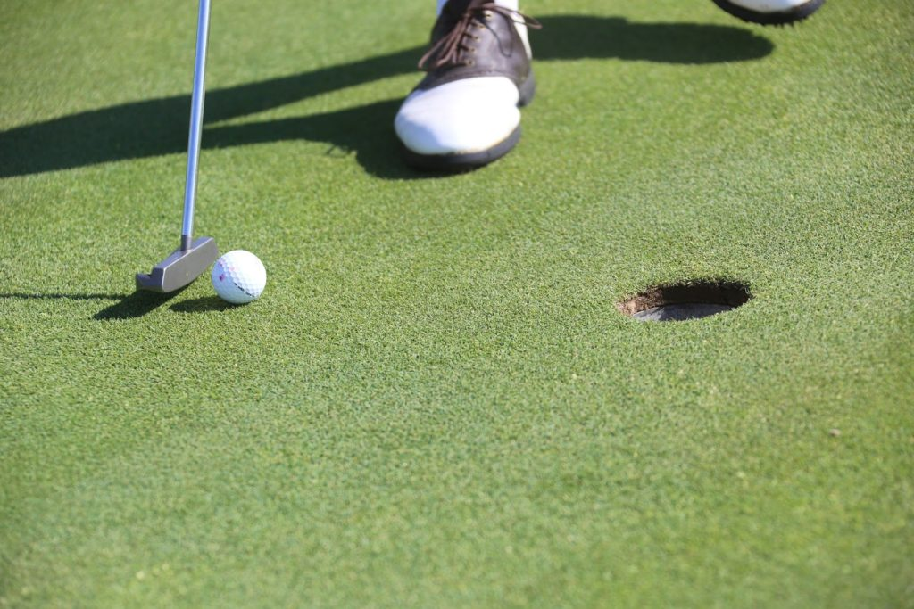 Putter hitting a golf ball toward a hole in a green with a man's foot visible in the background.