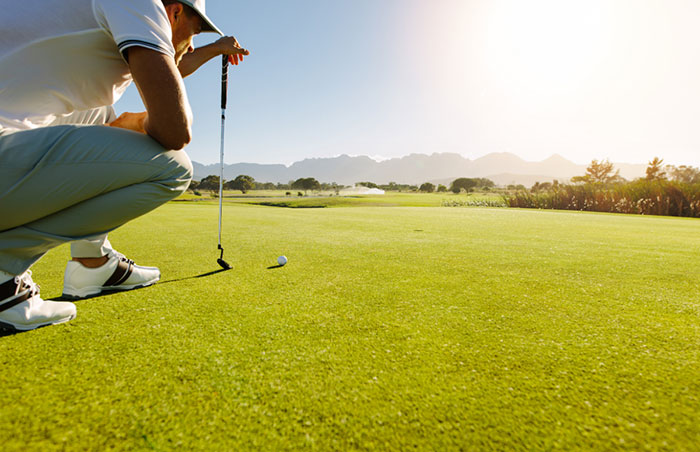 Golfer crouched above a golf ball on a sunny green.