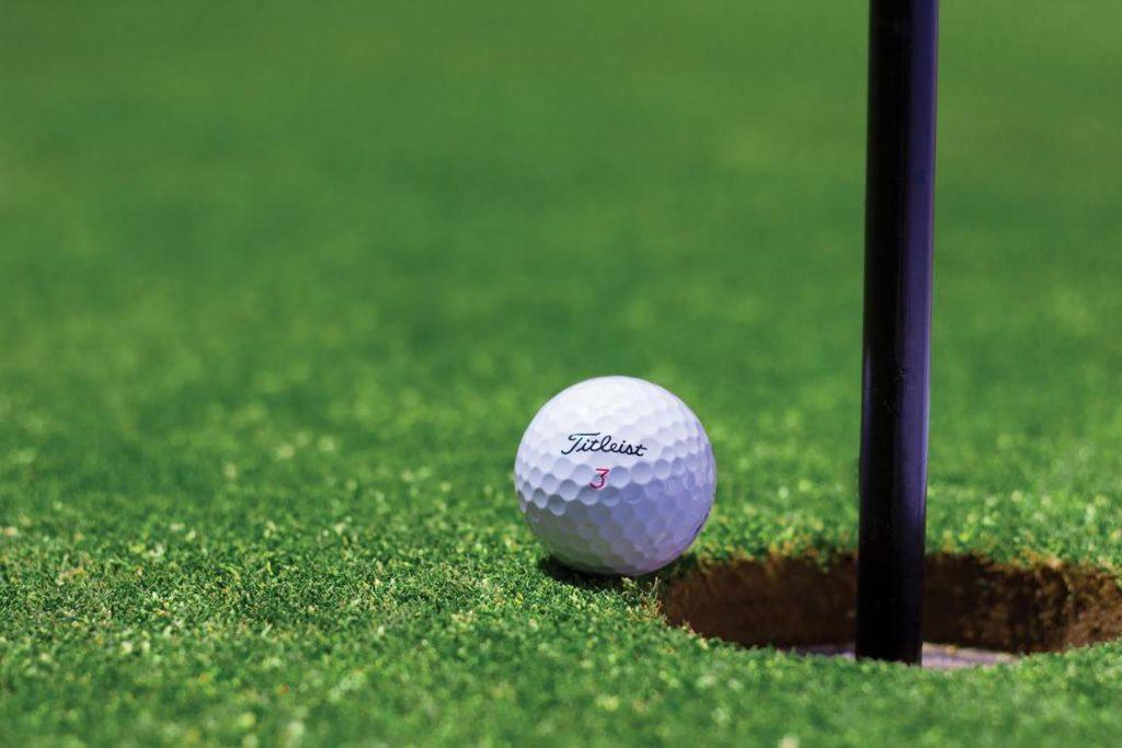 Titleist golf ball on a green next to a hole.