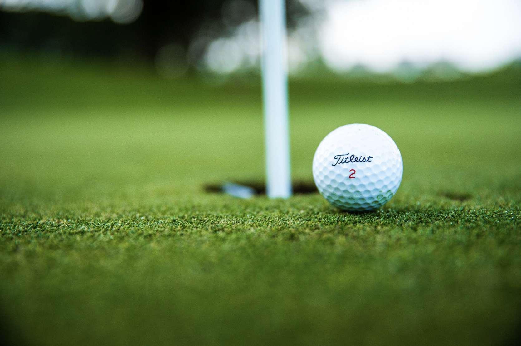 A black golf club resting against a golf ball on grass.