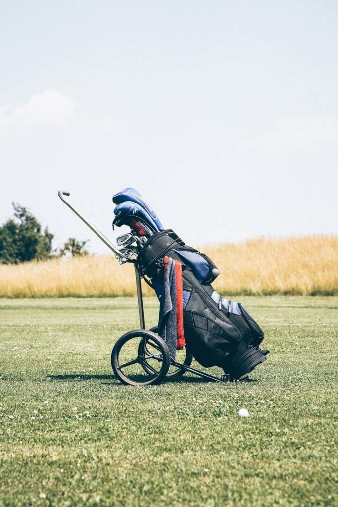 A packed golf bag on wheels standing on grass.