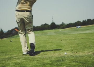 A golfer mid-swing, seen from the waist down.