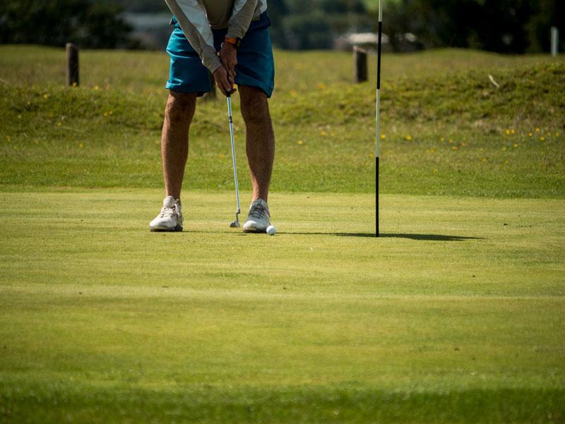 Golfer seen from the waist down putting a ball.