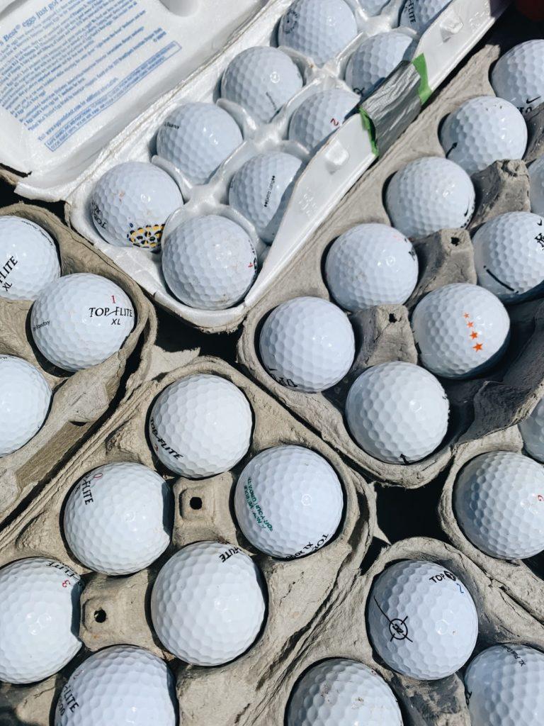 Cardboard egg cartons filled with golf balls.