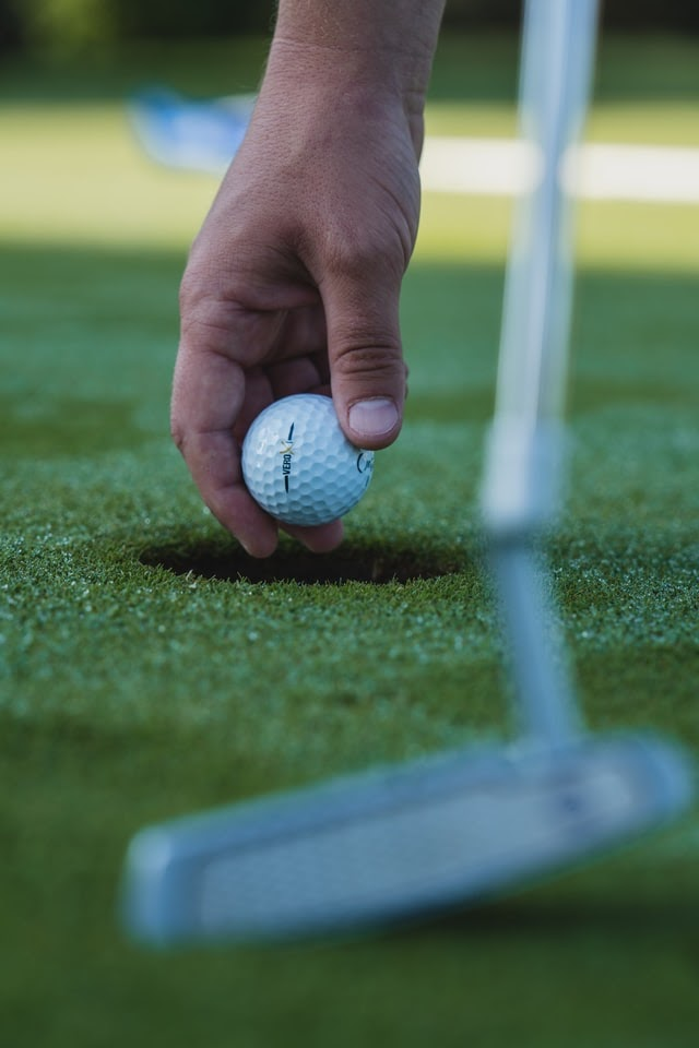 A hand holding a gold ball above a hole on a golf green.