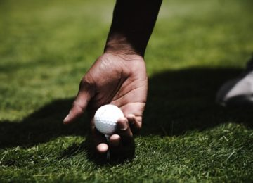 A golf tee in grass with a ball balanced on it and a hand grasping it.
