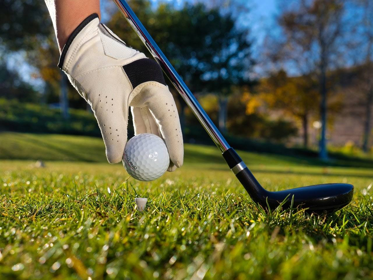 Gloved hand placing a golf ball on a tee.
