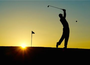 Silhouette of a golfer mid-swing in front of a sunset.