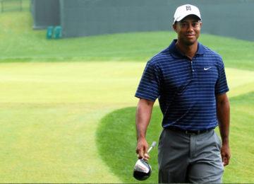 Pro golfer Tiger Woods walking on a green, holding a golf club.