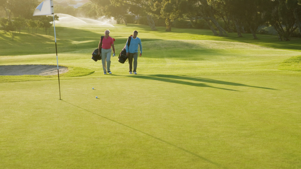 Two golfers walking on a golf course in the sun.