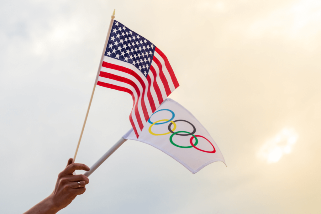 A hand holding an Olympic flag and a United States flag.