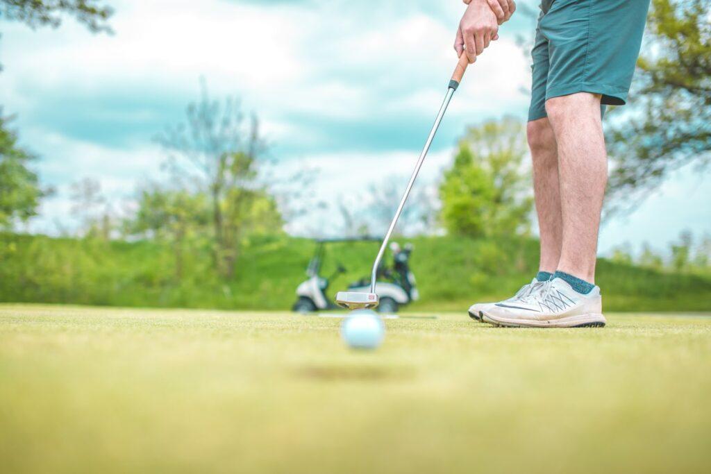 A golfer seen from the waist down hitting a ball along a green towards the viewer.