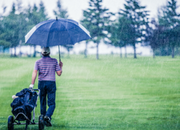 A golfer walking across a course in the rain, carrying an umbrella and wheeling a golf bag behind him.